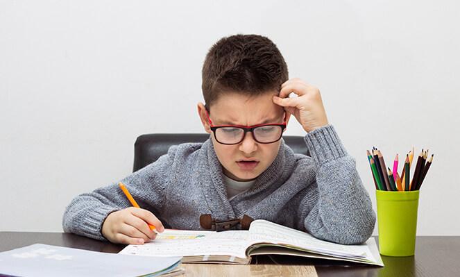 boy thinking hard to his homework